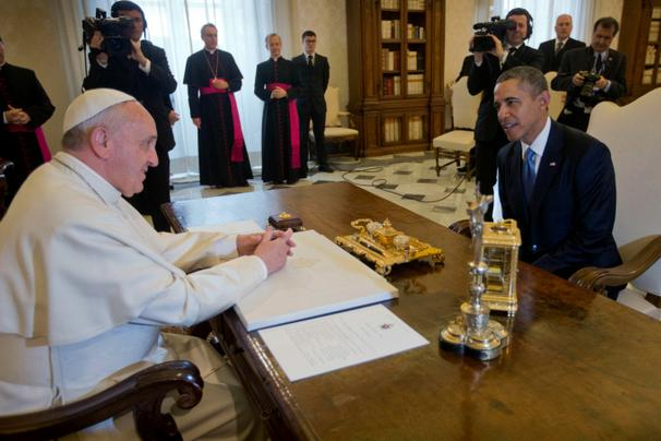 Obama and the Pope sitting at a desk