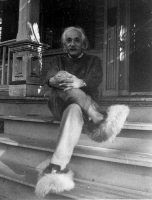 a black and white photo of Albert Einstein sitting on a front porch