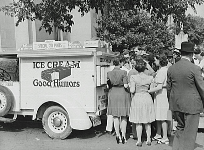 a black and white photo of people waiting in line for an ice cream truck