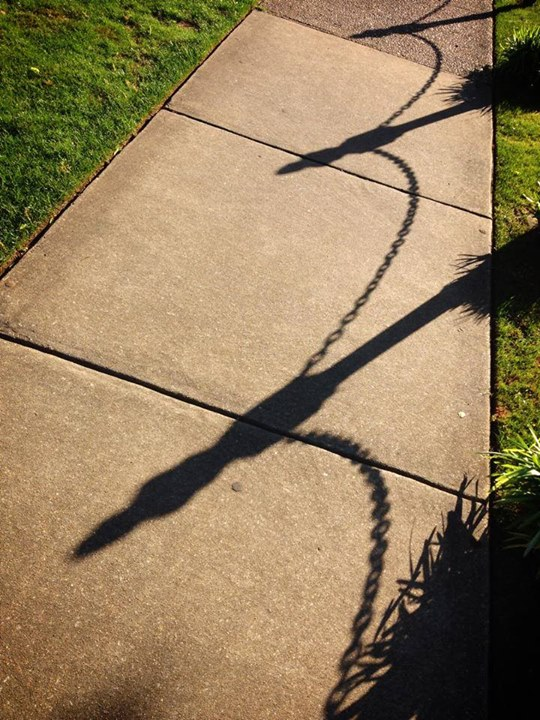 The shadow of chains on a sidewalk