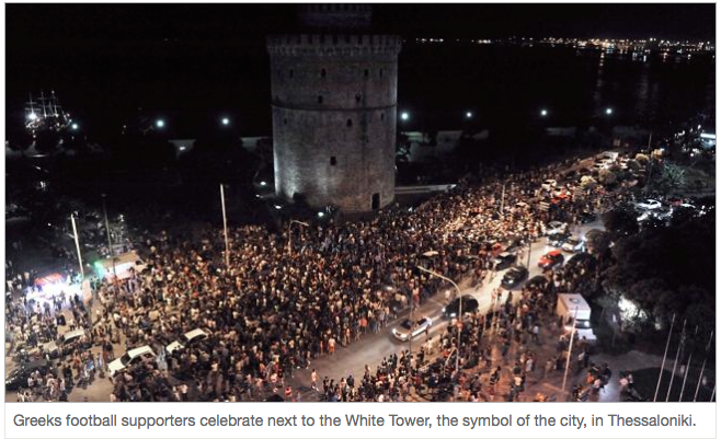 Greek football fans celebrate next to the White Tower