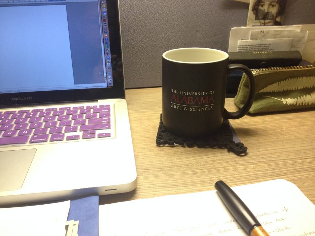 The University of Alabama mug on a desk along with a laptop and book