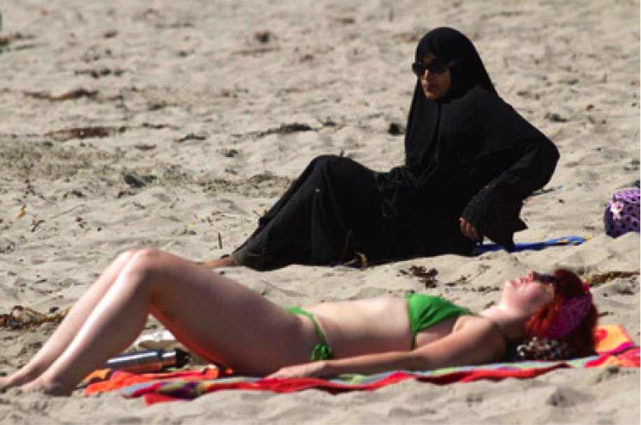 a woman in a bikini laying on the beach next to a woman covered from head to toe