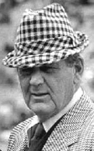 a black and white photo of Bear Bryant wearing a suit and plaid hat
