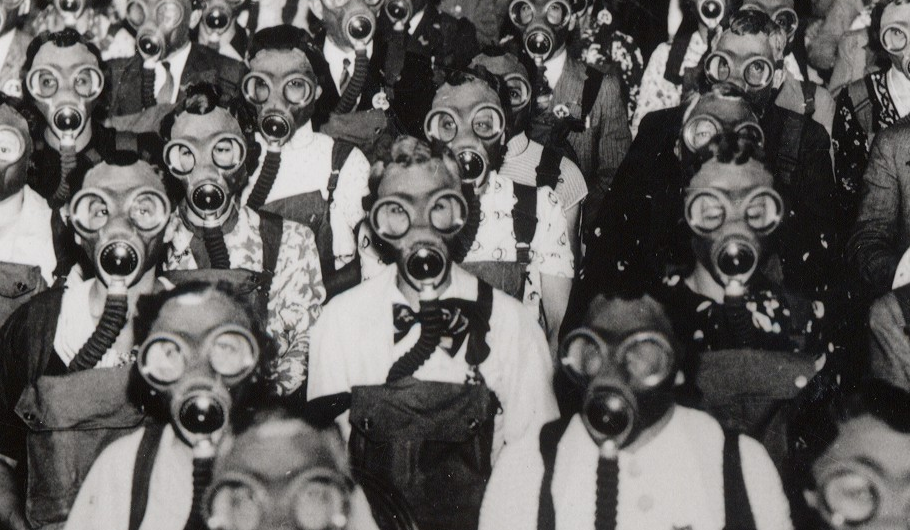 a black and white photo of a group of people wearing gas masks