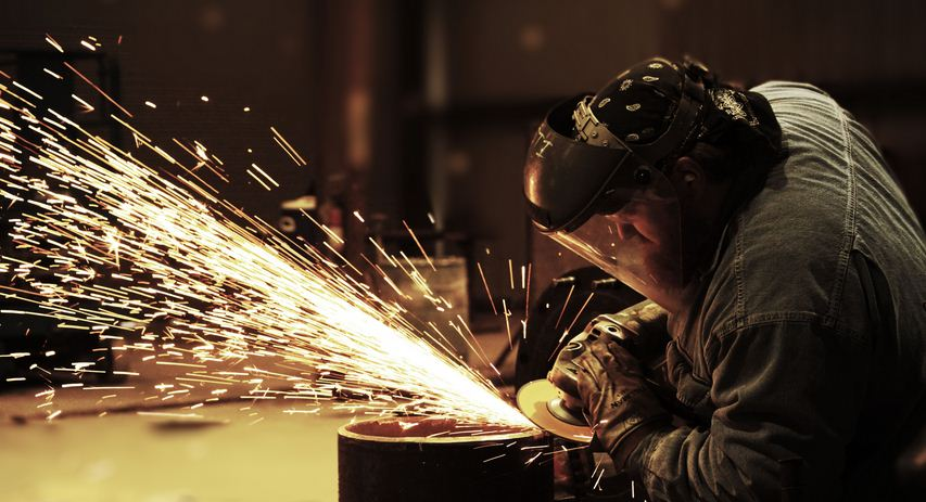A worker cutting with a saw while wearing protective gear