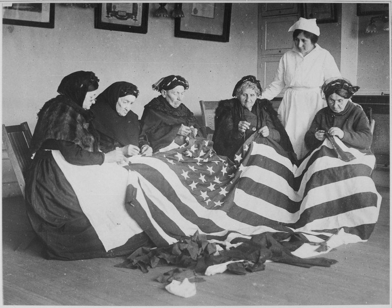 A black and white photo of five elderly women sewing the American flag