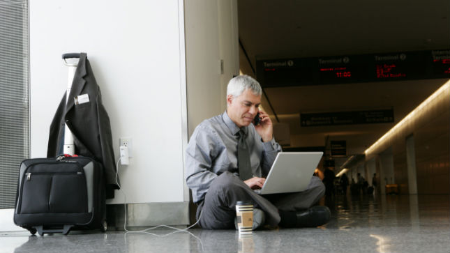 A man in an airport sitting on the ground on his phone and charging his laptop