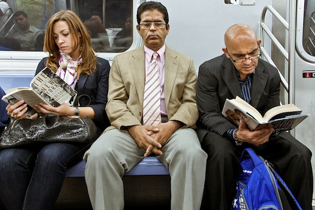 Three people sitting on the subway