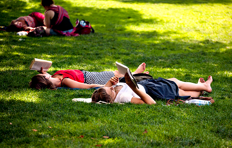 People laying in grass reading books