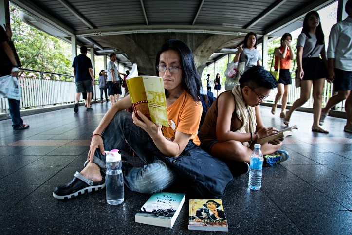 Two people sitting on the floor reading as people walk by them