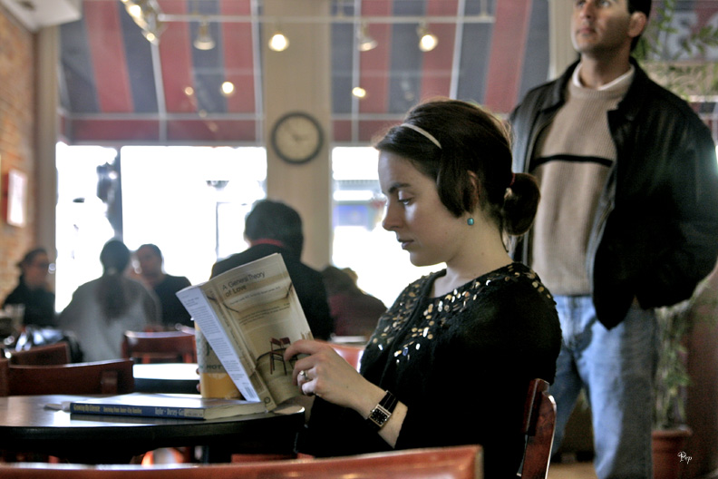 A girl reading a book in a cafe