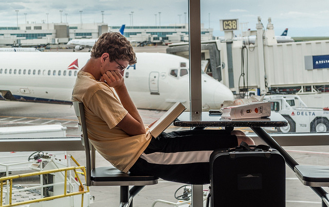 A teenage boy at an airport reading a book
