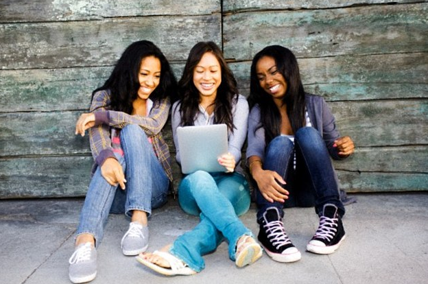 Three girls reading a tablet