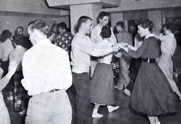 A black and white photo of men and women dancing