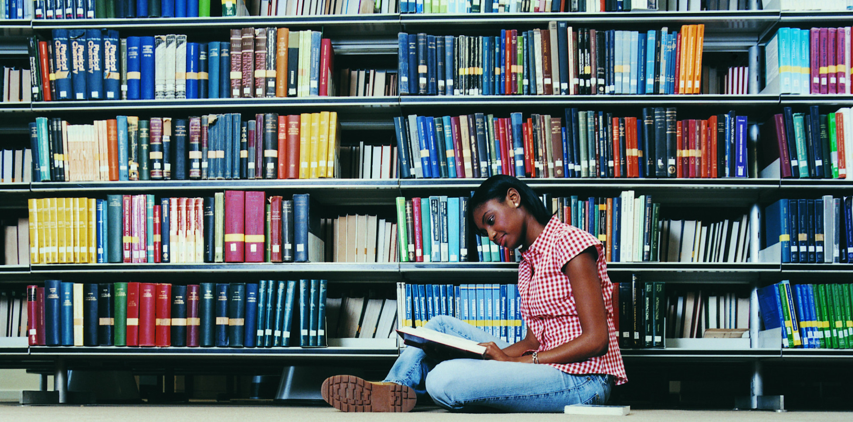A girl sitting on the floor reading a book in a library