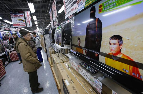 A man watching a tv in a store with hostages on the screen
