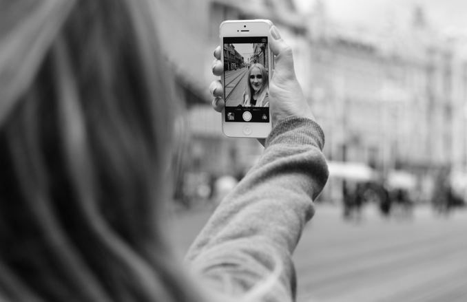 A black and white photo of a girl taking a selfie on her iphone
