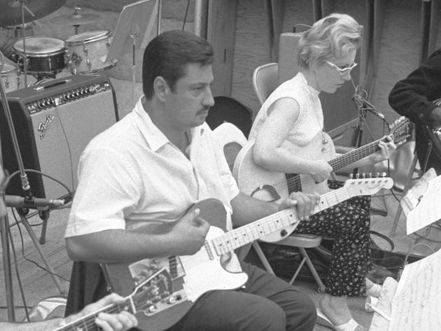 A black and white photo of a man and a woman playing the guitar