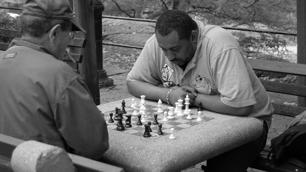 A black and white photo of two older men playing chess in a park