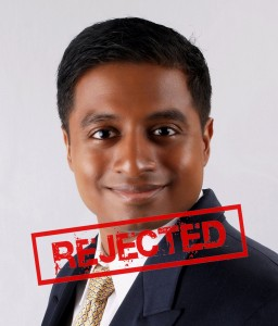"a black man in a suit with a red ""Rejected"" stamp across his photo"