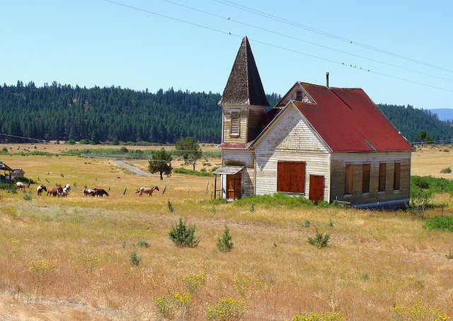 open land with a church and a bunch of horses