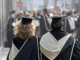 Two people wearing graduation gowns