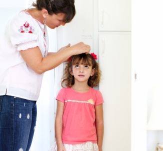 A woman measuring how tall a young girl is