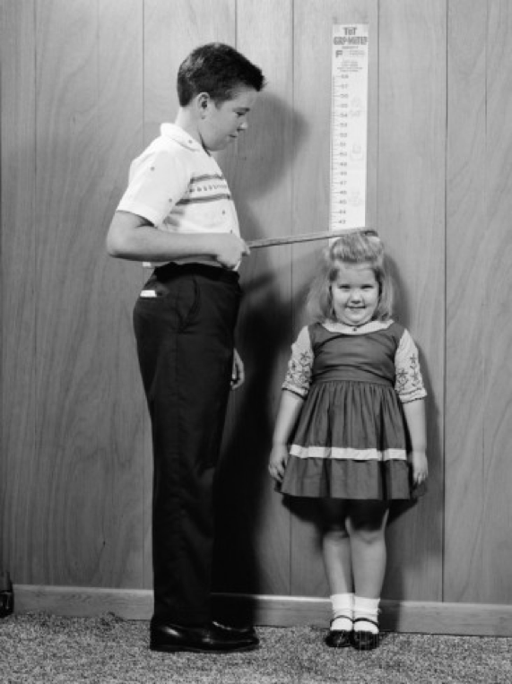 A young boy measuring a young girl against a wall