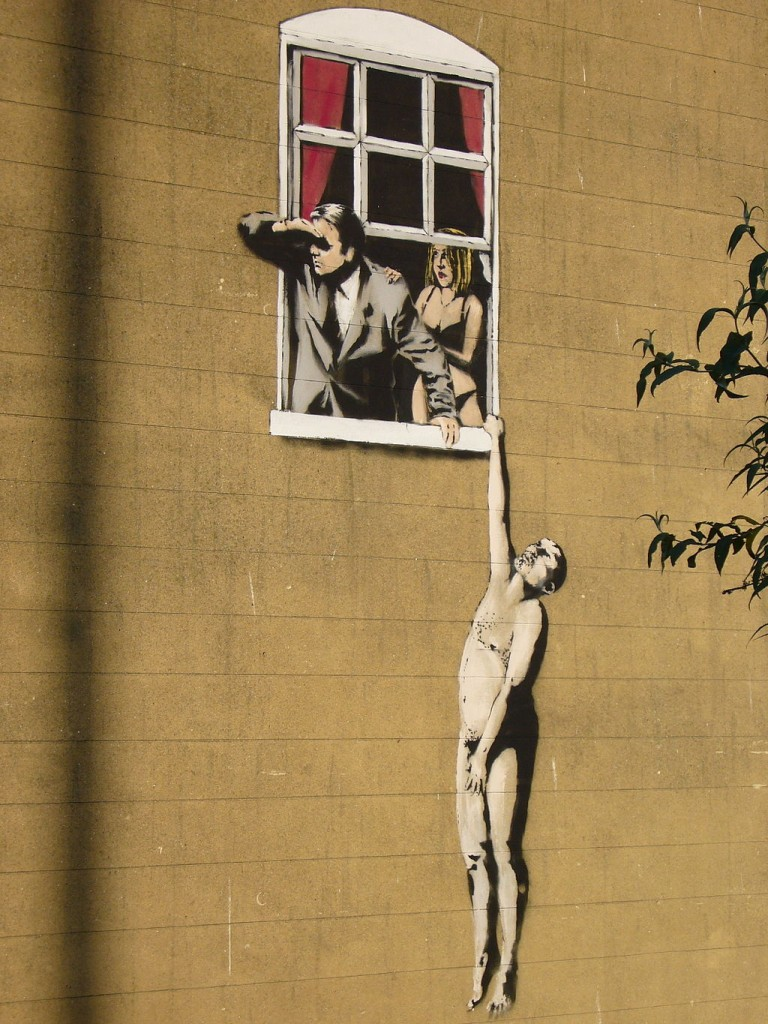 A man hanging off a window and a man and a woman looking out