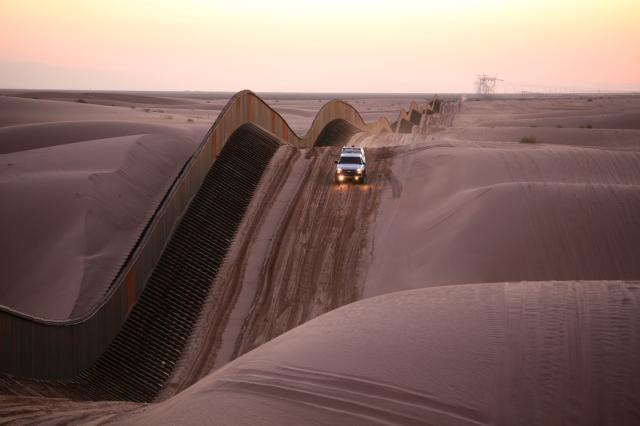 A truck driving down a sand dune