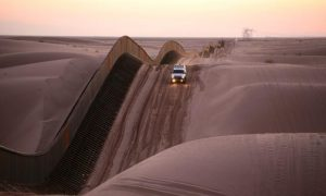 An image of a white truck driving down a sand dune
