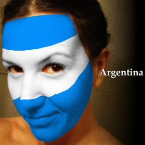 A woman with her face painted the colors of the Argentina Flag