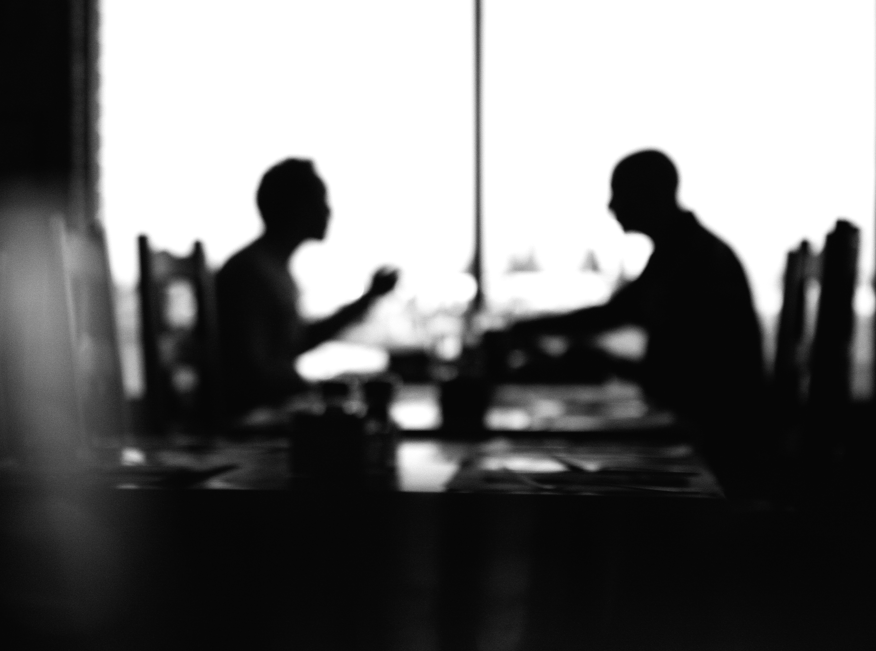 Two men sitting at a table having a conversation