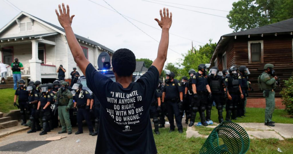 A man with his hands up standing in front of police