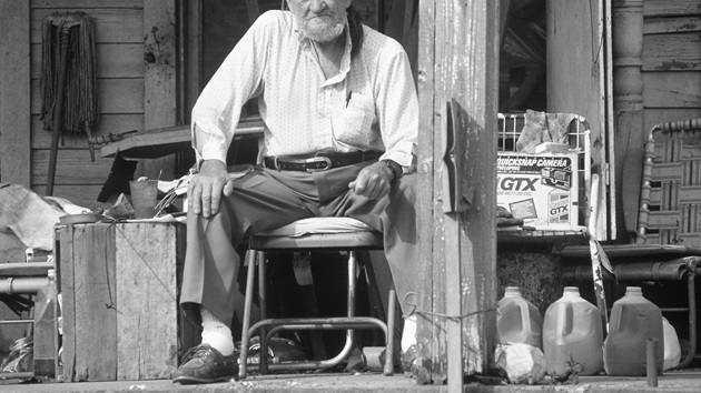 A black and white photo of an older man sitting on a chair