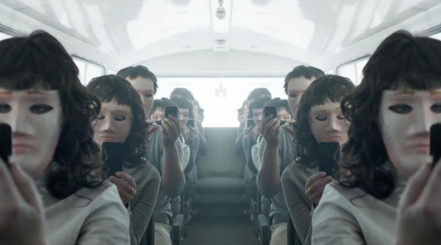 An image of men and women on a bus wearing masks and looking at their phones