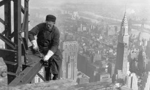 A black and white image of a man working on a building in New York city
