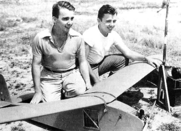 An image of an older photo of two young men working on an airplane
