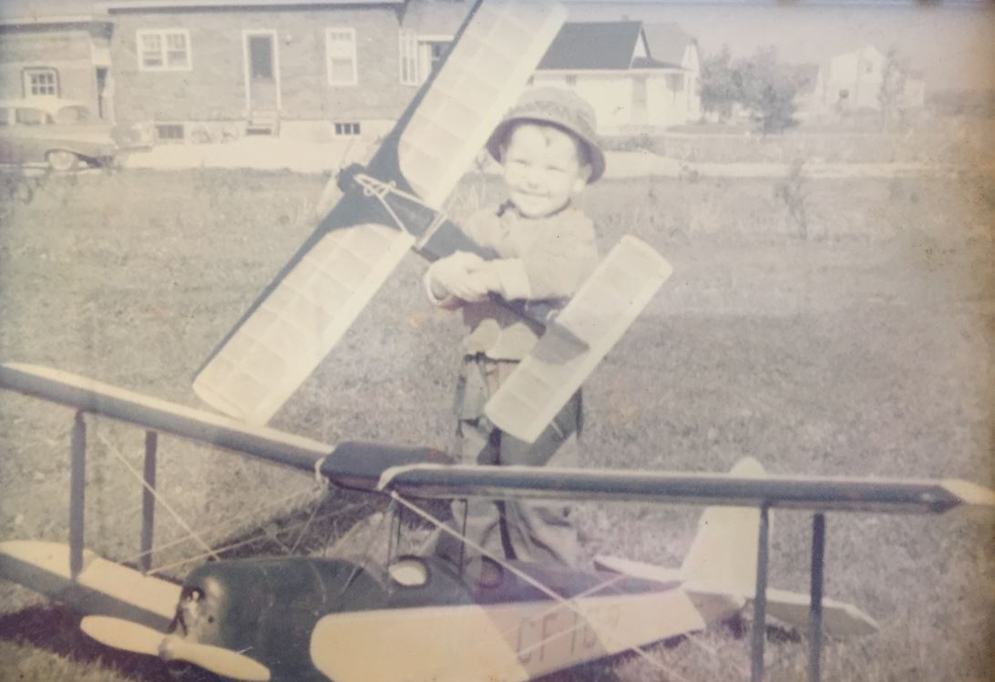 An image of a young boy playing with airplanes