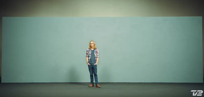 An image of a man standing in front of a blank wall