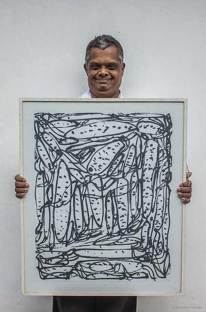 An image of a man holding a painting with black lines and dots