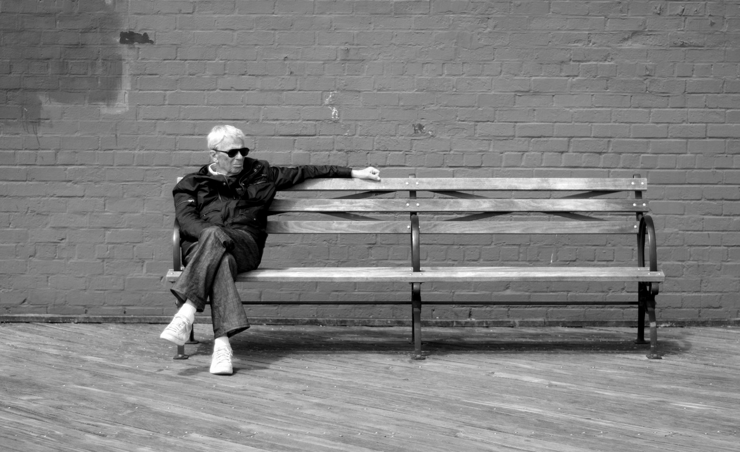 a man sitting on the edge of a bench