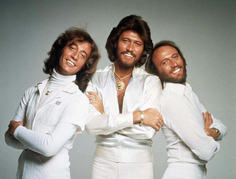 An image of 3 men dressed in white smiling