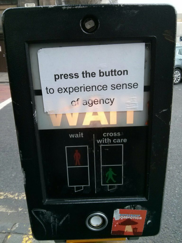 "crossing signal with a sign posted reading ""press the button to experience sense of agency"""