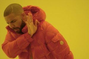"Drake with his right hand up beside his face. An image from his music video ""Hotline Bling"""