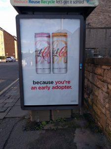 An image of a Diet Coke ad on a bus stop with the words