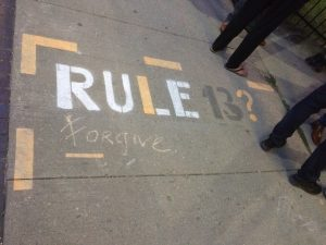 "Chalk writing on a sidewalk reading ""Rule 13? Forgive"""