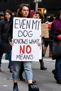 "person carrying sign that reads ""Even my dog knows what no means"""