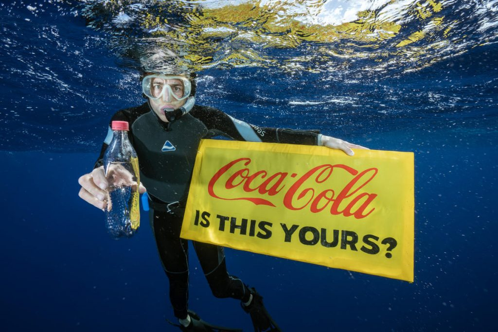 An image of a scuba diver holding a Coca Cola sign and a bottle (2)